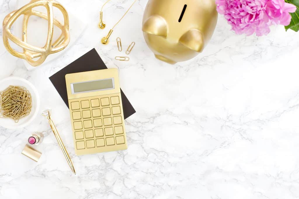 What is compound interest? A gold piggy bank and calculator on a table.